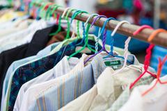 Old shirt hanging on plastic hangers - stock photo