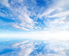 White fluffy clouds with rainbow in the blue sky Stock Photos