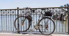Bike tied against railing of pier sidewalk Stock Photos