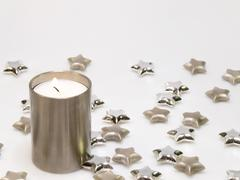 Decoration with burning candle and stars in silver - stock photo