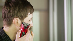 Young man shaves his beard with electric razor Stock Footage