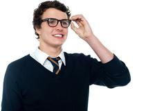 Smiling student adjusting his spectacles Stock Photos