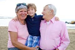 Happy cute kid hugging grandparents in vacation Stock Photos