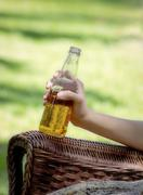 A Woman Holds a Glass Soda Bottle - stock photo