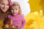 Mother and little daughter with basket and leaves Stock Photos