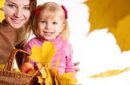 Mother and daughter with basket and leaves Stock Photos