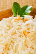 sauerkraut - Sour cabbage -  on wooden bowl with bay leaves - stock photo