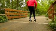 Stock Video Footage of View to man in sportswear with black red white rollerblades.