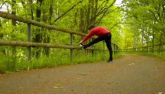 A closeup view to man in pink black sportswear run on road. Makes a stretching. Stock Footage