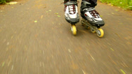 Stock Video Footage of A closeup view to legs in sportswear with black red white rollerblades.