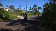 Stock Video Footage of Tourists on scooters / mopeds tour around traditional village, Kingdom of Tonga.