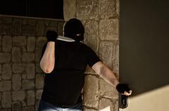 killer in balaclava ambushing behind a home door - stock photo