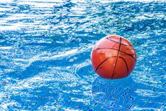 Dirty basketball on the swimming pool Stock Photos