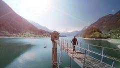 Man walking over bridge in lake panorama scenery Stock Footage