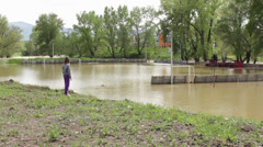 Floods. Environmental disaster. Little girl walking and watching flooding river. Stock Footage