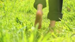 Child running barefoot on grass - stock footage