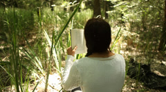 Young woman Reading a novel - Tracking Shot Stock Footage