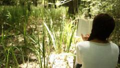 Woman Reading a Book - Tracking Shot Stock Footage