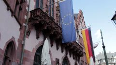 German and EU flag hanging from building Stock Footage