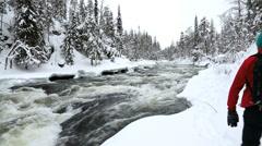 Male walker by river snowy spruce forest Oulanka Nat Pk  Finland Stock Footage
