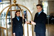 Stock Photo of Concierges holding the cart and posing