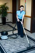 Staff cleaning carpet with a vacuum cleaner Stock Photos