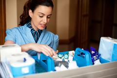 Pretty female housekeeper busy working - stock photo