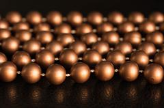 Some threads of brown beads on a black background Stock Photos