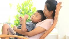 Mother and son sitting on rocking chair. - stock footage