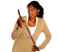 Surprised young woman looking to phone handset - stock photo