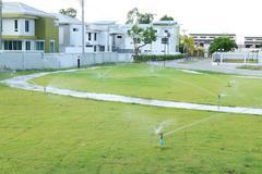water sprinkler spray watering in park. - stock photo