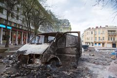 burned car in the center of city after unrest - stock photo