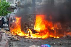 burning car in the center of city during unrest - stock photo