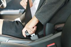 business woman hand fastening a seat belt. - stock photo