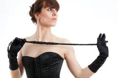 woman in a corset and  riding crop - stock photo