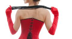woman in a red corset and whip - stock photo