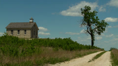 Kansas Flint Hills old stone Schoolhouse and road Stock Footage