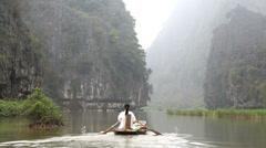 Vietnamese female rowing using her legs Tam Coc nr Ninh Binh nr Hanoi Stock Footage