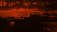 Beautiful red sunrise with moving clouds and sun breaking through the dark Stock Footage