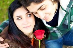 Romantic couple with rose in hand smiling Stock Photos