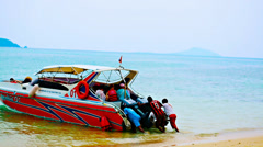 Man pushing a boat with tourists from the beach Stock Footage