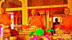 Three golden statues in a buddhist temple on a background of a lotus flower Stock Footage