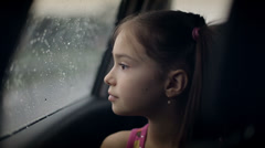 Little girl looking out from car window. Rainy weather - stock footage
