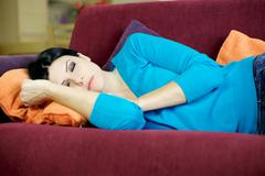 gorgeous woman sleeping relaxed on couch at home - stock photo