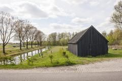black wooden shed near canal - stock photo