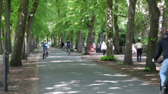 Bicycle riders in a city park Stock Footage