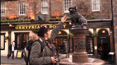 A girl stroking the nose of Greyfriars Bobby. Edinburgh Stock Footage