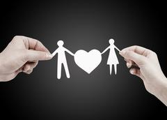 paper family in hands isolated on black background - stock photo