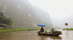 Senior male Vietnamese boat person and leg rowers in boats nr Hanoi Asia Stock Footage