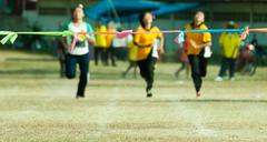 Child girl sprinting to finish line in sport day of school Stock Photos